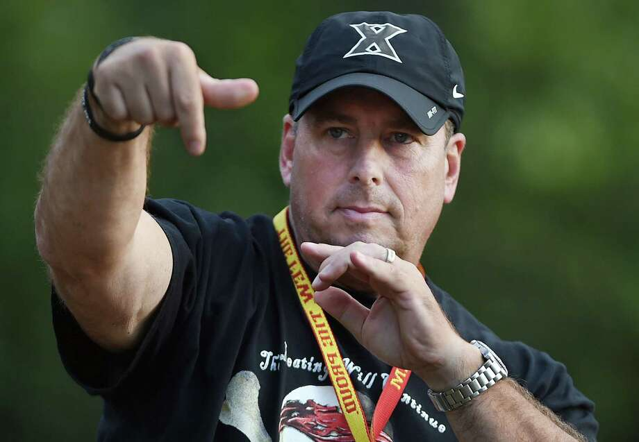 Catherine Avalone - The Middletown Press Xavier High School head football coach, Sean Marinan tosses the football at practice Thursday evening. Photo: Journal Register Co. / The Middletown Press