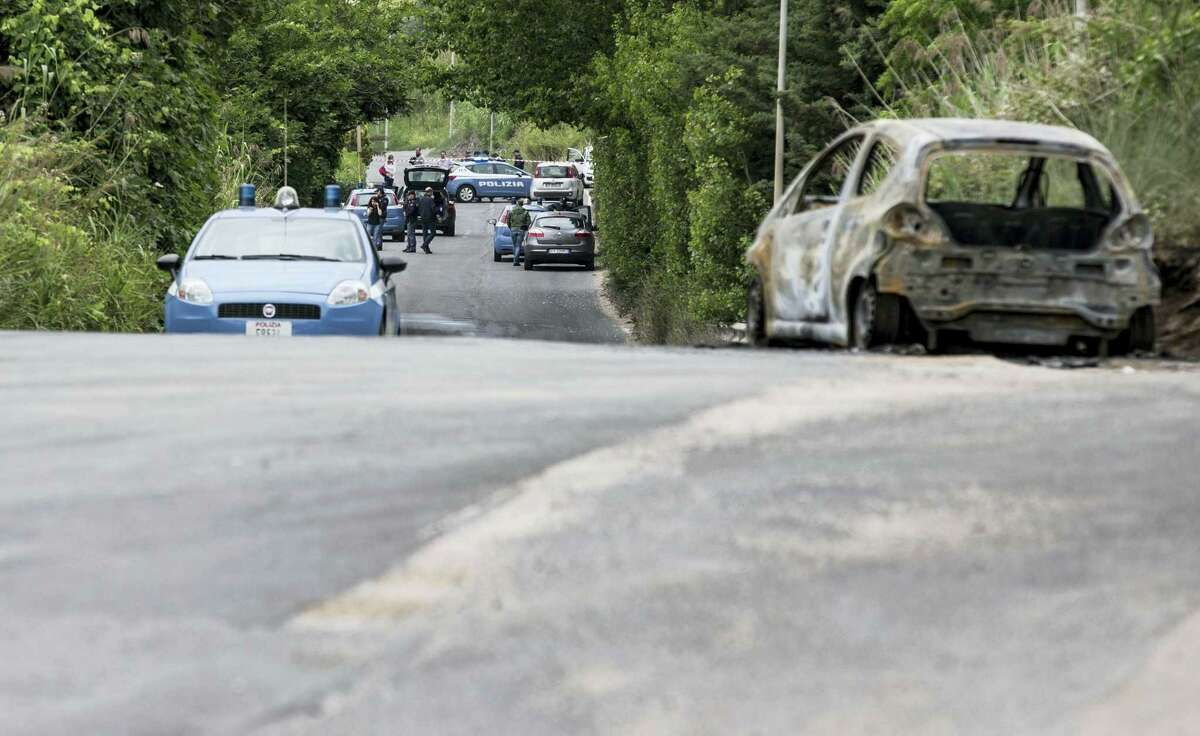 The burned car belonging to slain 22-year-old student Sara Di Pietrantonio is seen along a street in the outskirts of Rome, Monday, May 30, 2016. According to Italian police, Sara, whose body was found close to the car, had been burned alive by her ex-boyfriend as she was was trying to escape from him.
