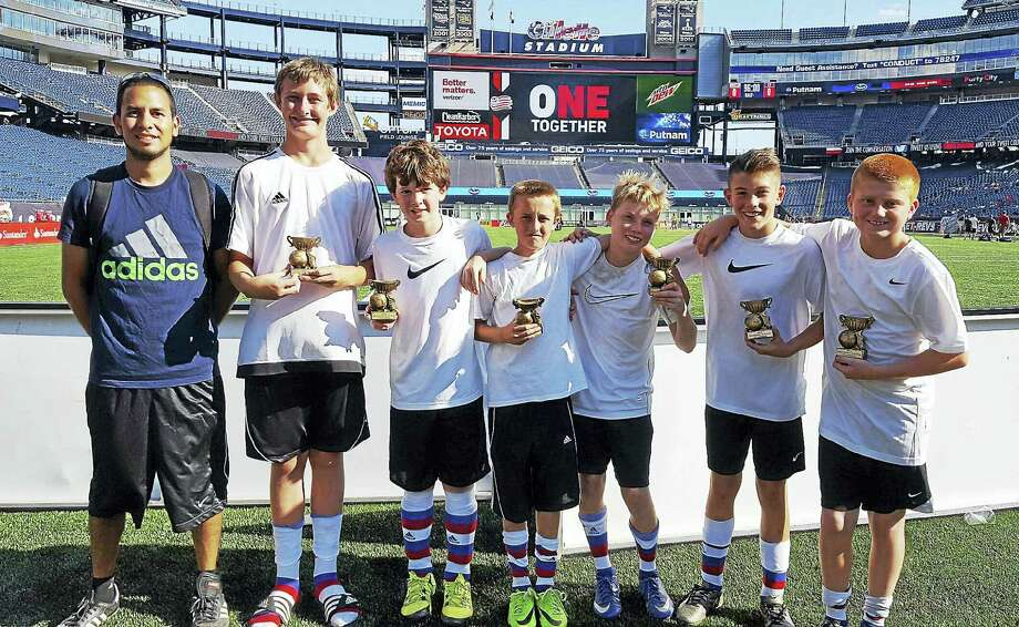 A local U12 six-player soccer team recently captured the Revolution 4v4 Cup tournament championship at Gillette Stadium in Foxboro, Mass. Over 200 teams from around the Northeast participated in the tourney, which was hosted by the MLS' New England Revolution. The boys, who play for a premier soccer team out of Middletown, were honored at halftime of the Revolution game. Pictured, from left, are Coach Andrew (AJ) Hodge of Middletown, Liam Scales, Connor Swanson, Sammy Johnson, Will McCarter, Beckett Hennessey, and Devin Juan. Photo: Submitted Photo
