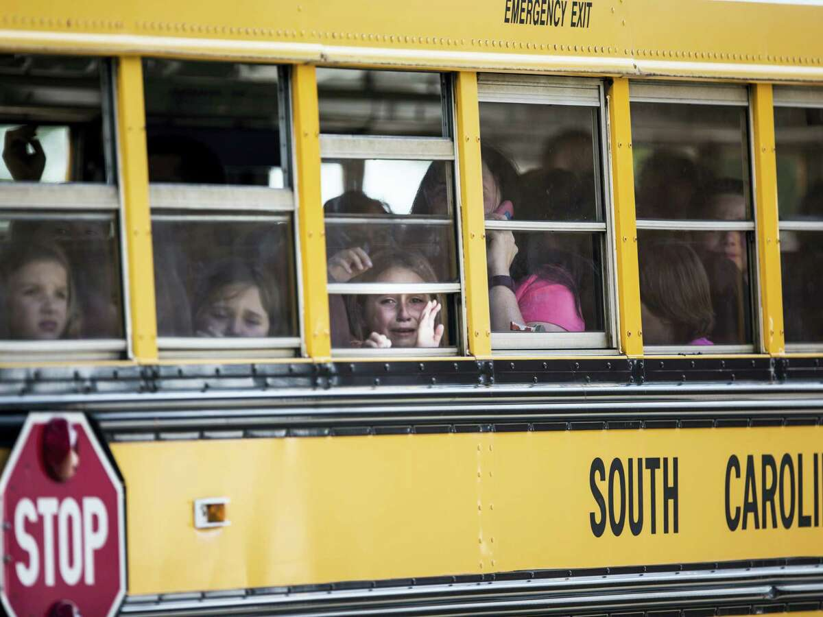 A Townville Elementary student looks out of the window of a school bus as she and her classmates are transported to Oakdale Baptist Church, following a shooting at Townville Elementary in Townville on Sept. 28, 2016. A teenager killed his father at his home Wednesday before going to the nearby elementary school and opening fire with a handgun, wounding two students and a teacher, authorities said.