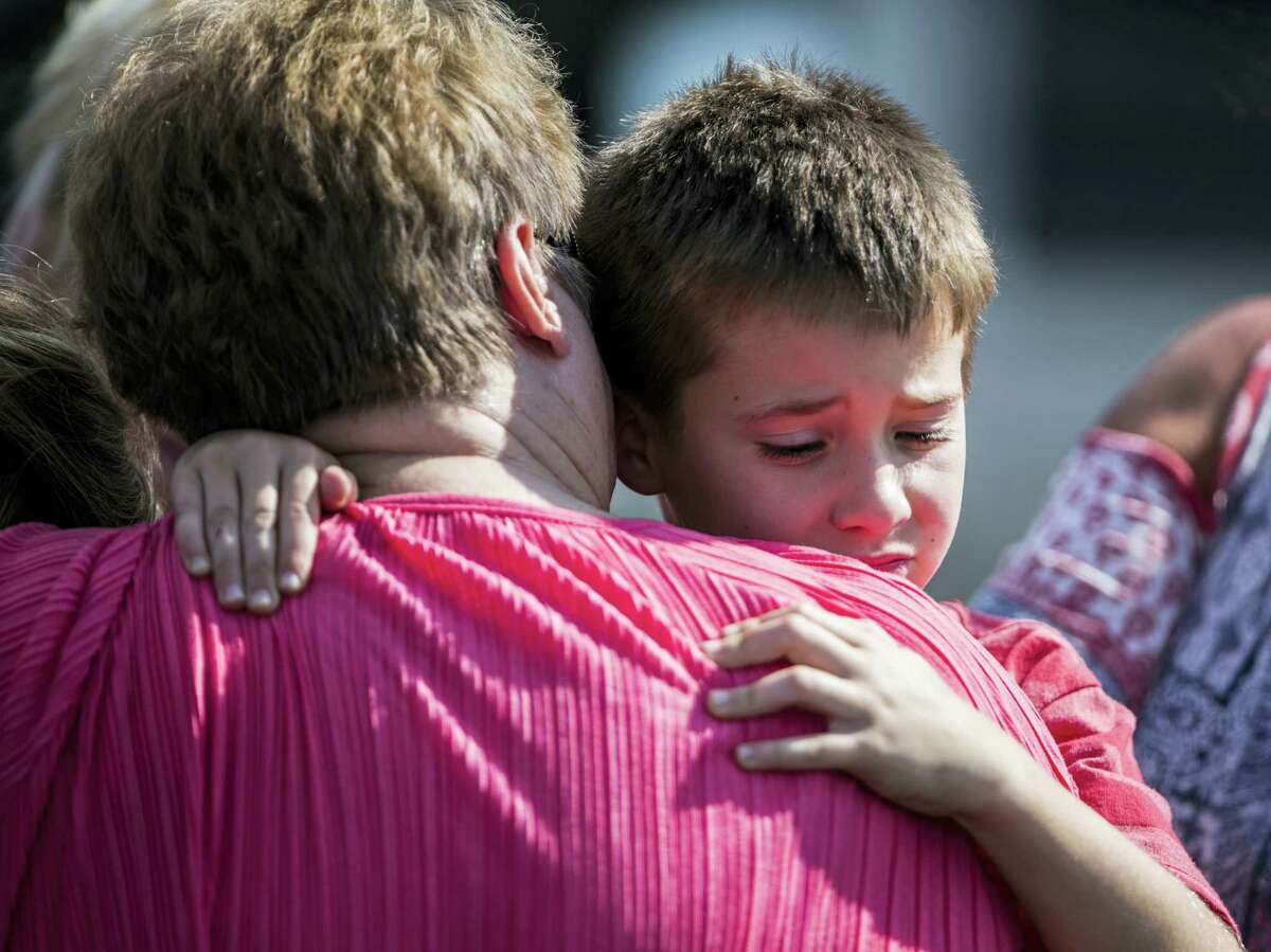A woman hugs a boy following a shooting at Townville Elementary in Townville on Sept. 28, 2016. A teenager killed his father at his home Wednesday before going to the nearby elementary school and opening fire with a handgun, wounding two students and a teacher, authorities said.