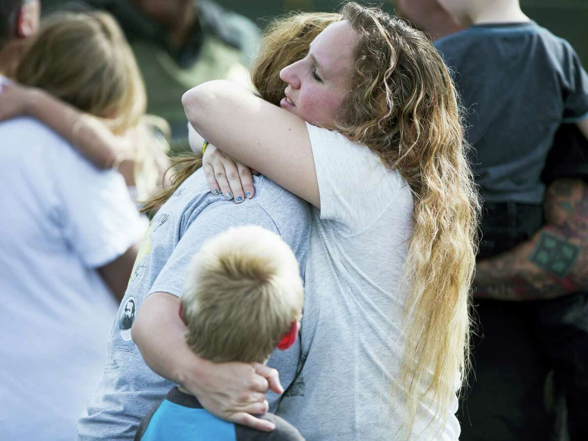 Korrie Bennett hugs Heather Bailey after recovering their children following a shooting at Townville Elementary in Townville Wednesday, Sept. 28, 2016. A teenager killed his father at his home Wednesday before going to the nearby elementary school and opening fire with a handgun, wounding two students and a teacher, authorities said. (Katie McLean/The Independent-Mail via AP)