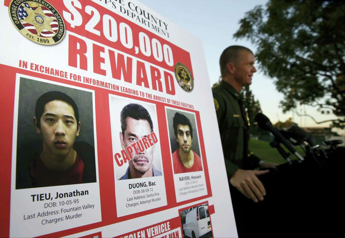 """Orange County Sheriff's Department Public Information Officer Lt. Jeff Hallock, right, says escaped inmate Bac Duong, marked """"Captured,"""" middle, surrendered in Orange County earlier Friday, Jan. 29, 2016, during a news conference in Santa Ana, Calif. Duong told investigators he was with the other two fugitives in San Jose, Calif., on Thursday. Hallock says the other two men, Jonathan Tieu and Hossein Nayeri, may now be headed to Fresno in Central California, where there may be associates who can help them. Authorities had previously said they thought all three men were still in Southern California."""