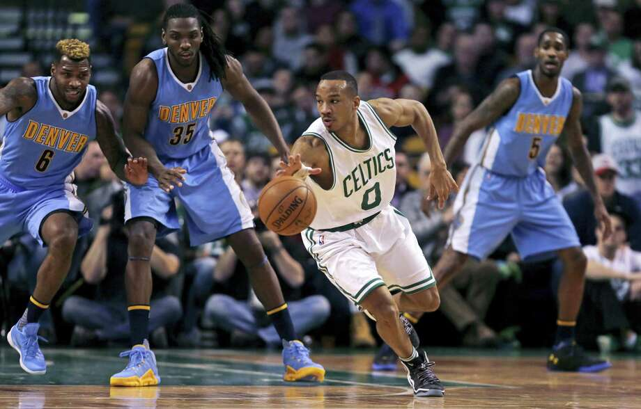 Boston Celtics guard Avery Bradley (0) looks to pass as he threads through the Denver Nuggets' defense during the second half of an NBA basketball game in Boston, Wednesday, Jan. 27, 2016. Boston won 111-103. (AP Photo/Charles Krupa) Photo: AP / AP