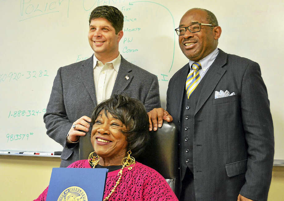 Jazz vocalist Kitty Kathryn of Middletown, seated, was named the new music ambassador on Tuesday in a presentation at City Hall that included (standing) Mayor Dan Drew, left; and the Rev. Moses Harvill of Cross Street AME Zion Church, right. Photo: Cassandra Day — The Middletown Press
