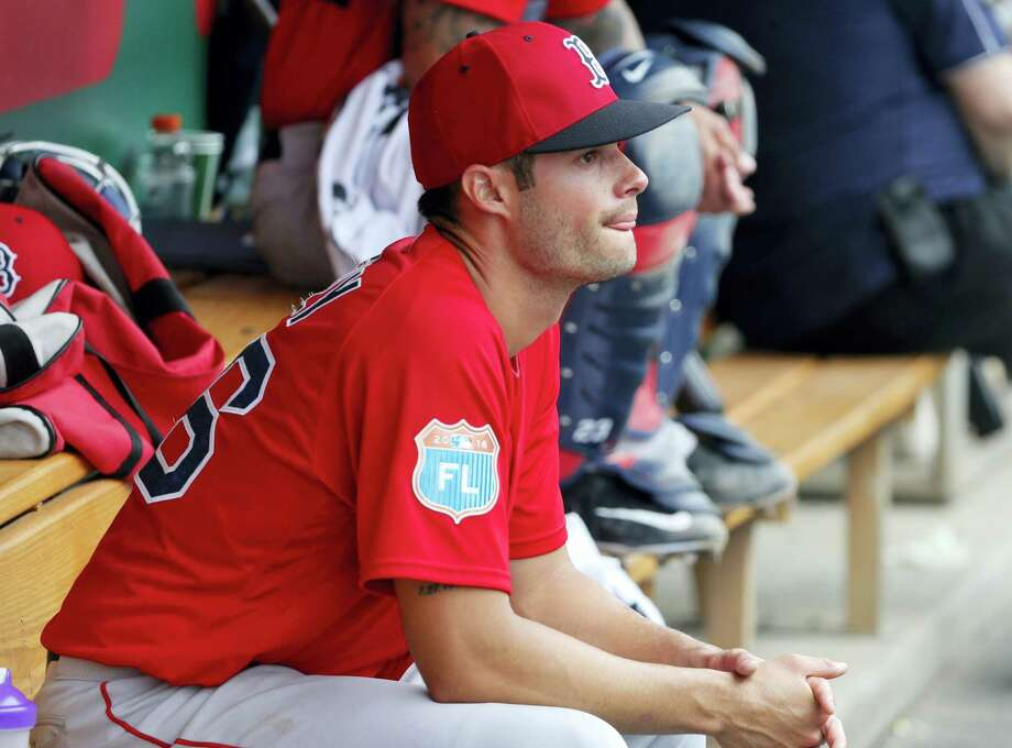 Joe Kelly sits in the dugout in the third inning on Tuesday. Photo: Tony Gutierrez — The Associated Press  / AP