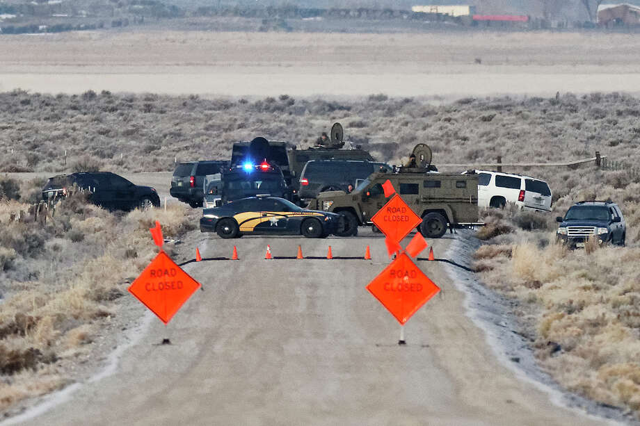 Law enforcement personnel block an access road to the Malheur National Wildlife Refuge, Wednesday, Jan. 27, 2016, near Burns, Ore. Authorities were restricting access on Wednesday to the Oregon refuge being occupied by an armed group after one of the occupiers was killed during a traffic stop and eight more, including the group's leader Ammon Bundy, were arrested. Photo: Thomas Boyd/The Oregonian Via AP   / The Oregonian