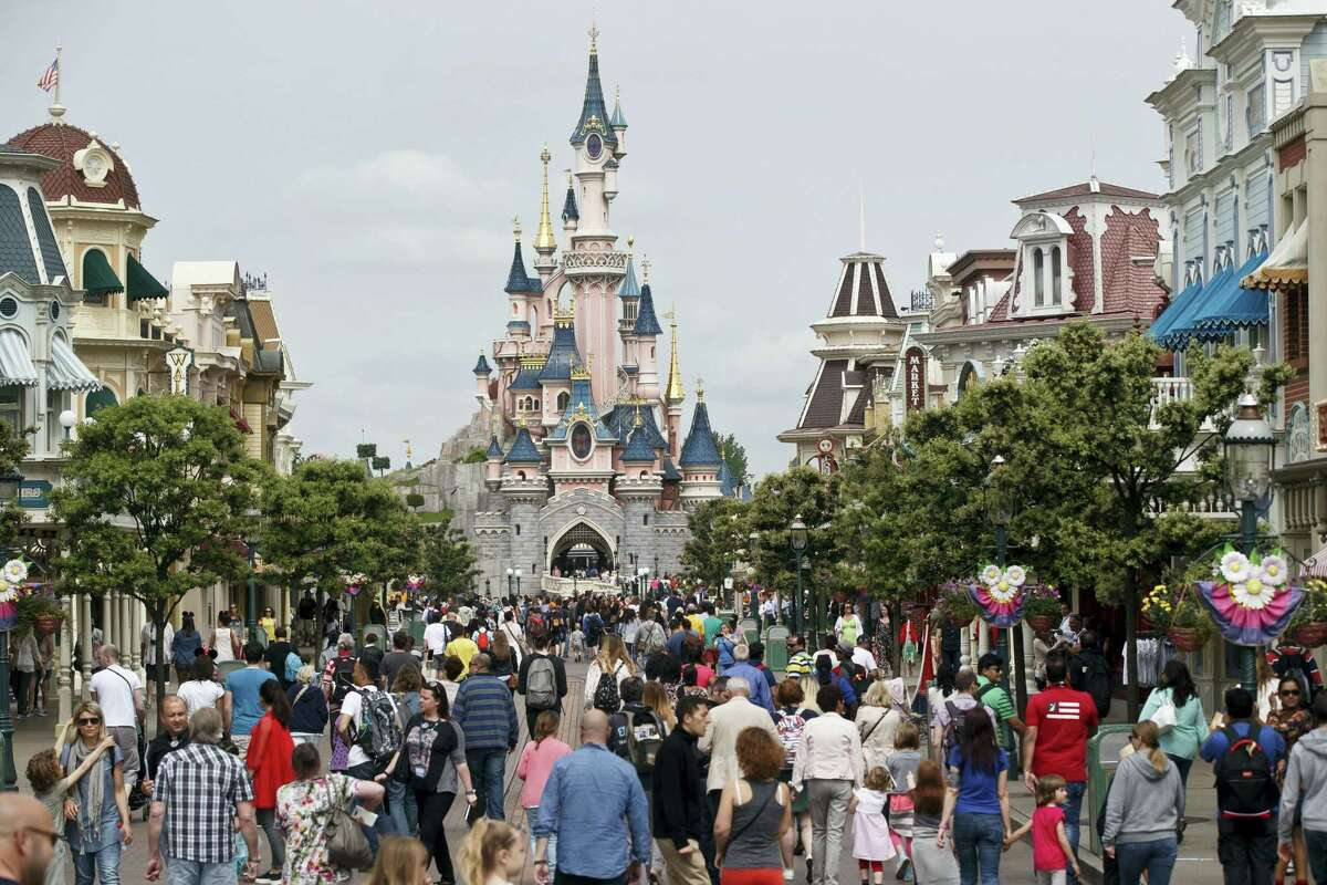 This Tuesday, May 12, 2015, file photo shows visitors walking toward the Sleeping Beauty's Castle, background, at Disneyland Paris in Marne la Vallee, east of Paris, France. A French police official says a man found to be carrying two handguns has been arrested at a hotel at Disneyland Paris. France remains under a state of emergency since Nov. 13 Islamic extremist attacks around Paris that killed 130 people.