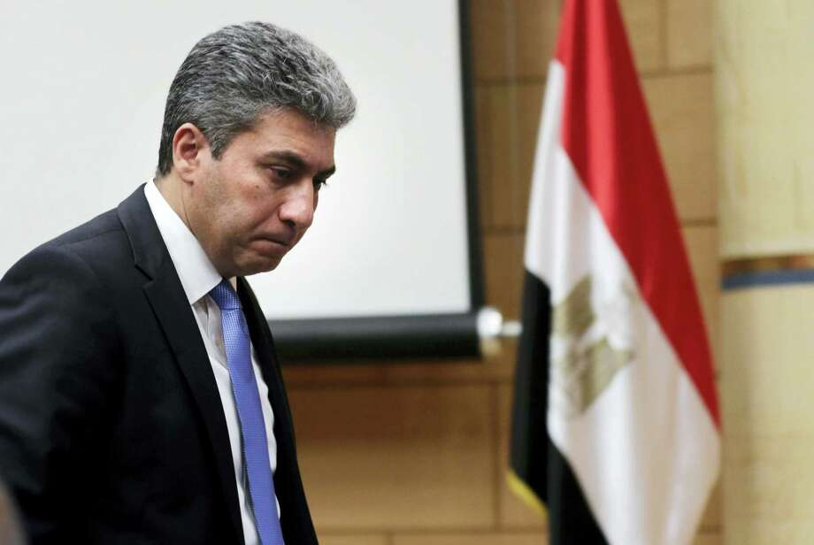 Egyptian Minister of Civil Aviation Sharif Fathy leaves a press conference at the Ministry headquarters in Cairo, Egypt on March 29, 2016. Fathy said seven people remain with the hijacker on the EgyptAir plane that has landed in Cyprus, four crew and three passengers. Photo: AP Photo/Amr Nabil  / AP