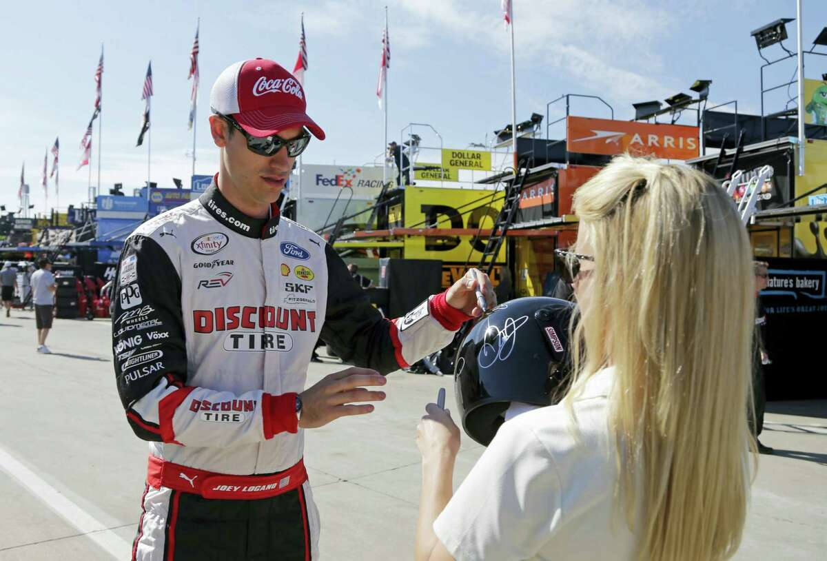 Joey Logano, left, signs an autograph before practice for Sunday's Coca-Cola 600.