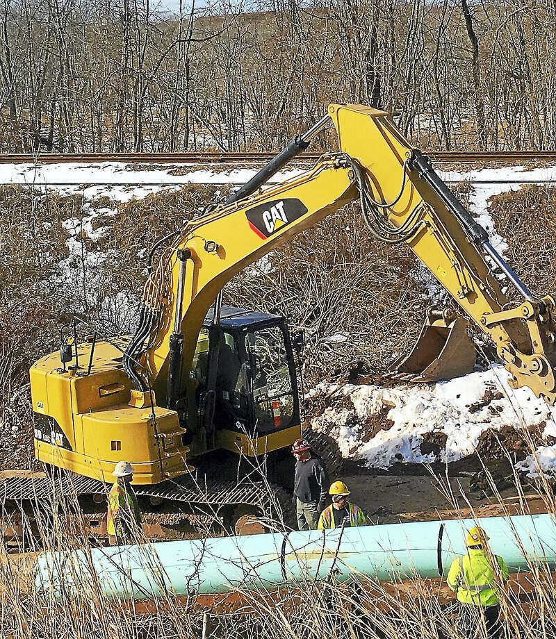 Construction workers can be seen from Route 9 working on the horizontal directional drilling pipe under the Mattabassett River at the Middletown-Cromwell line. Photo: Sam Norton — The Middletown Press