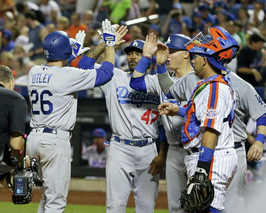 Mets catcher Rene Rivera (44) watches as the Dodgers' Chase Utley (26) celebrates with teammates after hitting a grand slam in the seventh inning on Saturday. Photo: Frank Franklin II — The Associated Press   / Copyright 2016 The Associated Press. All rights reserved. This material may not be published, broadcast, rewritten or redistribu