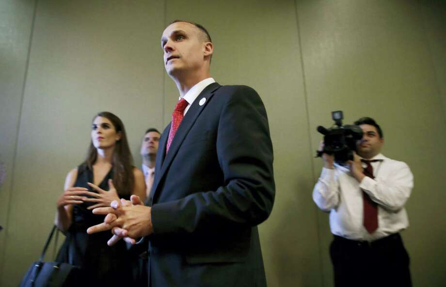 In this photo taken Aug. 25, 2015, Republican presidential candidate Donald Trump's campaign manager Corey Lewandowski watches as Trump speaks in Dubuque, Iowa. Florida police have charged Lewandowski with simple battery in connection with an incident earlier in the month involving a reporter. Photo: AP Photo — Charlie Neibergall / AP
