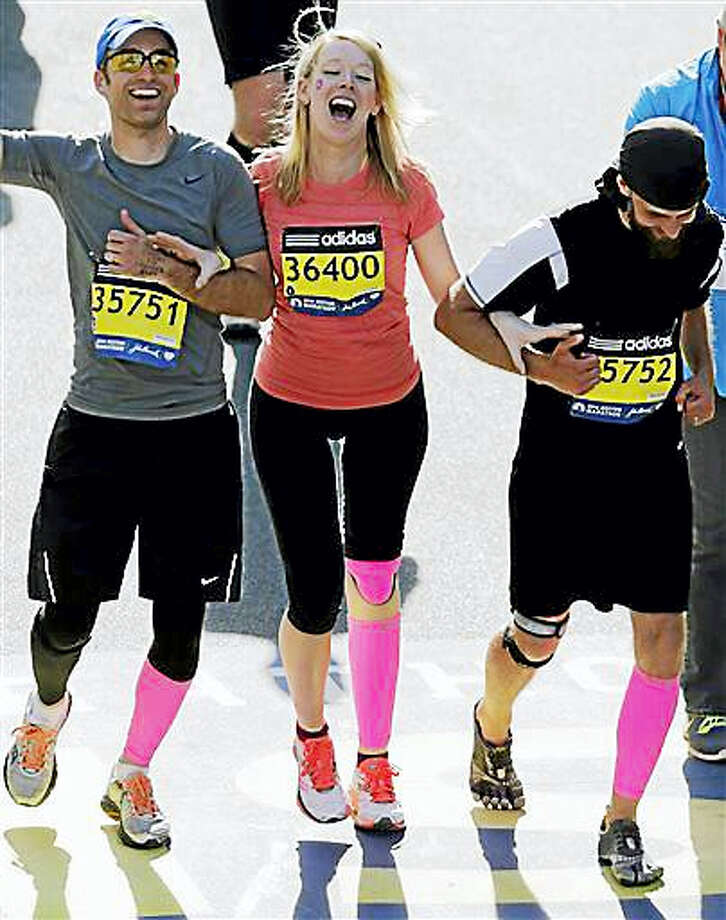 In this April 21, 2014, file photo, Timothy Haslet, left, and David Haslet, right, celebrate with their sister Adrianne Haslet-Davis at the finish line of the 118th Boston Marathon, after she completed a short distance of the course in Boston. Haslet-Davis said she is training to run the entire Boston Marathon on Monday, April 18, 2016. Haslet-Davis lost her left leg below the knee in the April 2013 bombing attacks, which killed three people and wounded more than 260 others. Photo: AP Photo/Charles Krupa, File   / AP