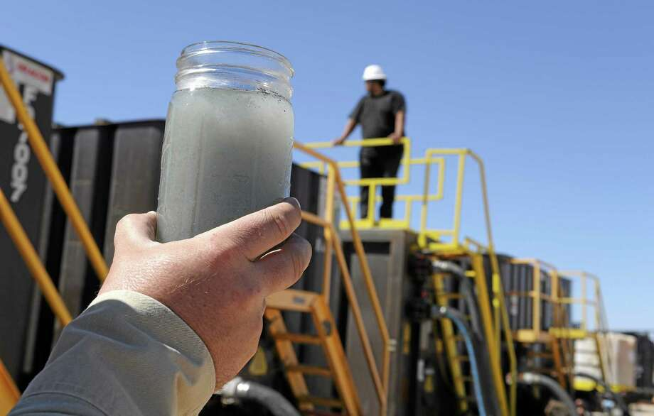A jar holding waste water from hydraulic fracturing is held up to the light at a recycling site. Photo: File Photo  / AP