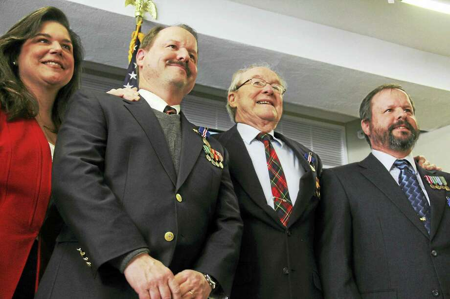 State Sen. Danté Bartolomeo poses alongside a Middletown father, William Simmons, center, and his two sons — Peter Simmons, left, and Robert Simmons — who were among more than 75 individuals given the Connecticut Veterans Wartime Service Medal Tuesday at the senior center. Photo: Kathleen Schassler — The Middletown Press  / Kathleen Schassler All Rights
