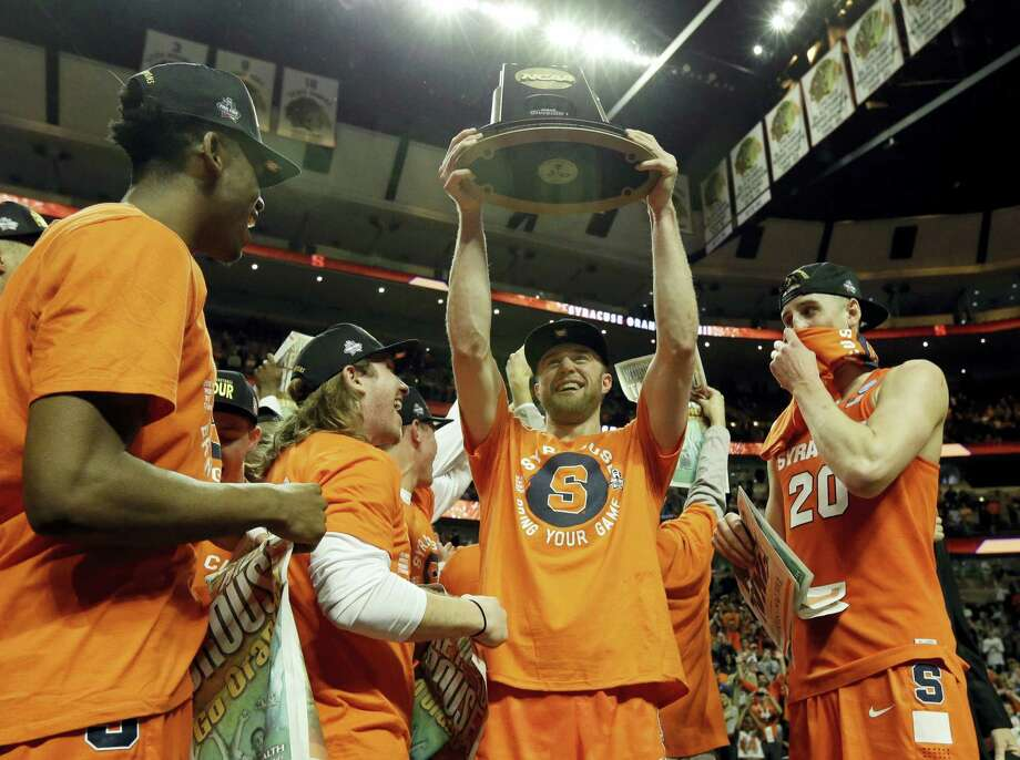 Nam Y. Huh — The Associated Press Syracuse's Trevor Cooney holds up the championship trophy as he celebrate with his teammates after the Orange defeated top-seeded Virginia in the regional final Sunday in Chicago. Syracuse won 68-62. Photo: AP / Huh