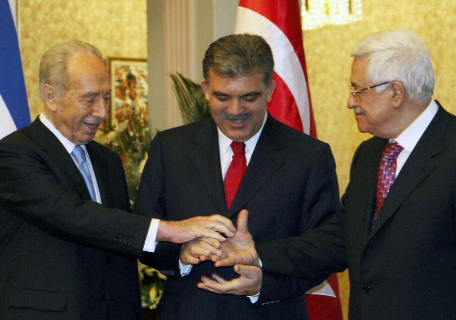 In this Tuesday file photo, Presidents Shimon Peres of Israel, left, Abdullah Gul of Turkey, center, and President of the Palestinian Authority Mahmoud Abbas try to reach hands as they pose for cameras after their meeting in Ankara. Peres, a former Israeli president and prime minister, whose life story mirrored that of the Jewish state and who was celebrated around the world as a Nobel prize-winning visionary who pushed his country toward peace, has died, the Israeli news website YNet reported early Wednesday. He was 93. Photo: Burhan Ozbilici — The Associated Press File  / Copyright 2016 The Associated Press. All rights reserved.