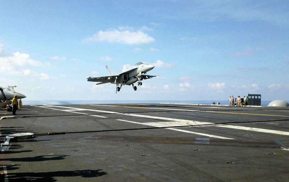 In this Friday, April 15, 2016, file photo, an FA-18 jet fighter lands on the USS John C. Stennis aircraft carrier in the South China Sea while U.S. Defense Secretary Ash Carter visited the aircraft carrier during a trip to the region.  (AP Photo/Lolita C. Baldor, File) Photo: AP / Copyright 2016 The Associated Press. All rights reserved. This material may not be published, broadcast, rewritten or redistribu