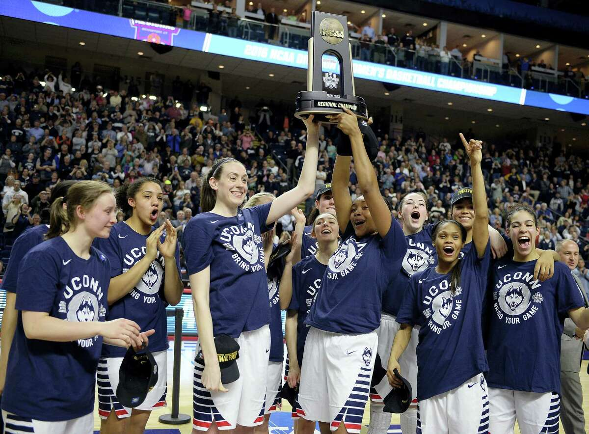 UConn's Breanna Stewart, left, and Morgan Tuck celebrate with the trophy and teammates after defeating Texas 86-65 in the championship game of the Bridgeport Regional. UConn won its 73rd consecutive game to earn its record ninth straight Final Four berth.