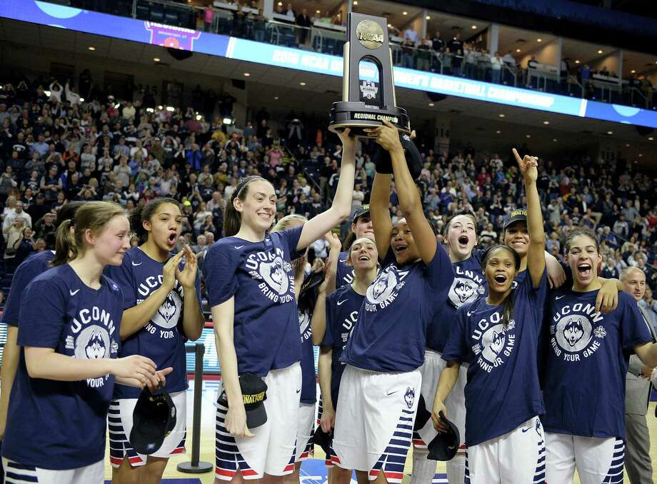 UConn's Breanna Stewart, left, and Morgan Tuck celebrate with the trophy and teammates after defeating Texas 86-65 in the championship game of the Bridgeport Regional. UConn won its 73rd consecutive game to earn its record ninth straight Final Four berth. Photo: Jessica Hill — The Associated Press  / FR125654 AP