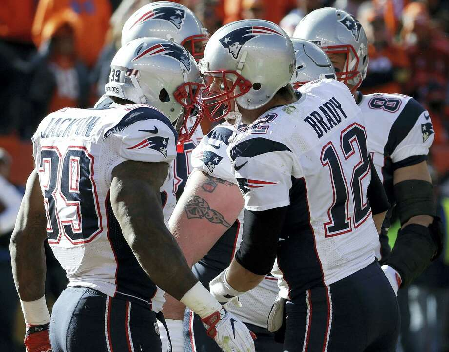 New England Patriots running back Steven Jackson (39) is congratulated by Tom Brady after scoring on a touchdown on a one-yard run during the first half Sunday. Photo: The Associated Press  / AP