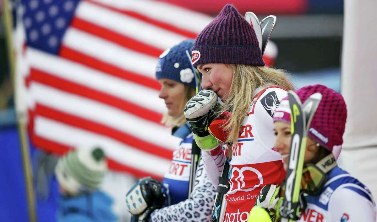 Mikaela Shiffrin holds her glove to her face and smiles towards her grandmother while standing on the podium after winning the alpine skiing women's World Cup slalom in Killington, Vt. on Sunday.
