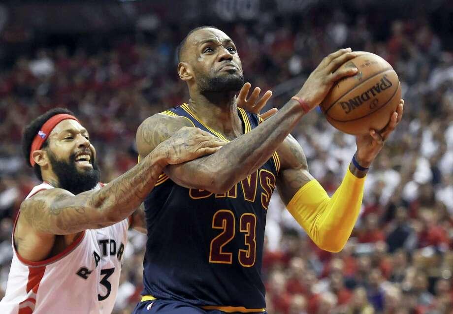 Raptors forward James Johnson fouls LeBron James late in the fourth quarter on Friday. Photo: Frank Gunn — The Canadian Press Via AP  / The Canadian Press