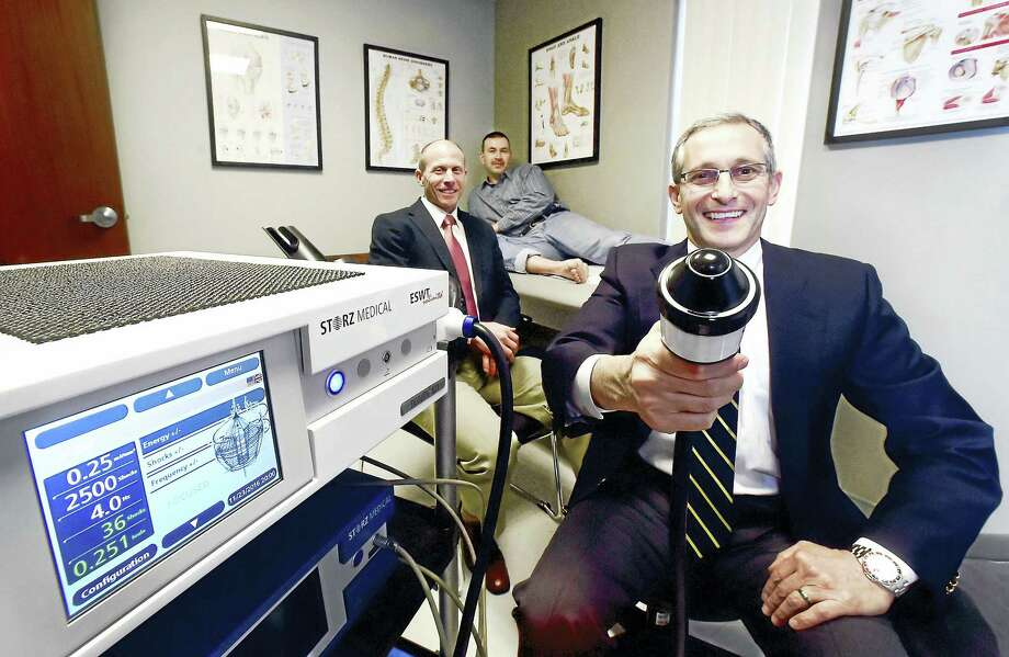 Foot and ankle specialists Dr. Jeffrey DeLott, left, and Dr. David Caminear, right, of Connecticut Orthopaedic Specialists display the Duolith SD1 shock-wave therapy machine used to treat the Achilles tendon inflammation of patient Alex Horjatschun, center. Photo: Peter Hvizdak — New Haven Register  / ?2016 Peter Hvizdak