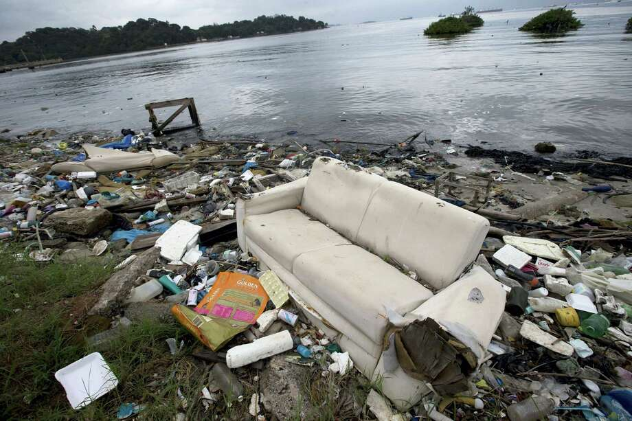 "In this June 1, 2015 file photo, a discarded sofa litters the shore of Guanabara Bay in Rio de Janeiro, Brazil. About 1,600 athletes will compete in Rio during the 2016 Summer Olympics. Hundreds more will be involved during the subsequent Paralympics. Experts say athletes will be competing in the viral equivalent of raw sewage with exposure to dangerous health risks almost certain. Many sailors have described the conditions as ""sailing in a toilet"" or an ""open sewer."" Photo: AP Photo/Silvia Izquierdo, File   / AP"