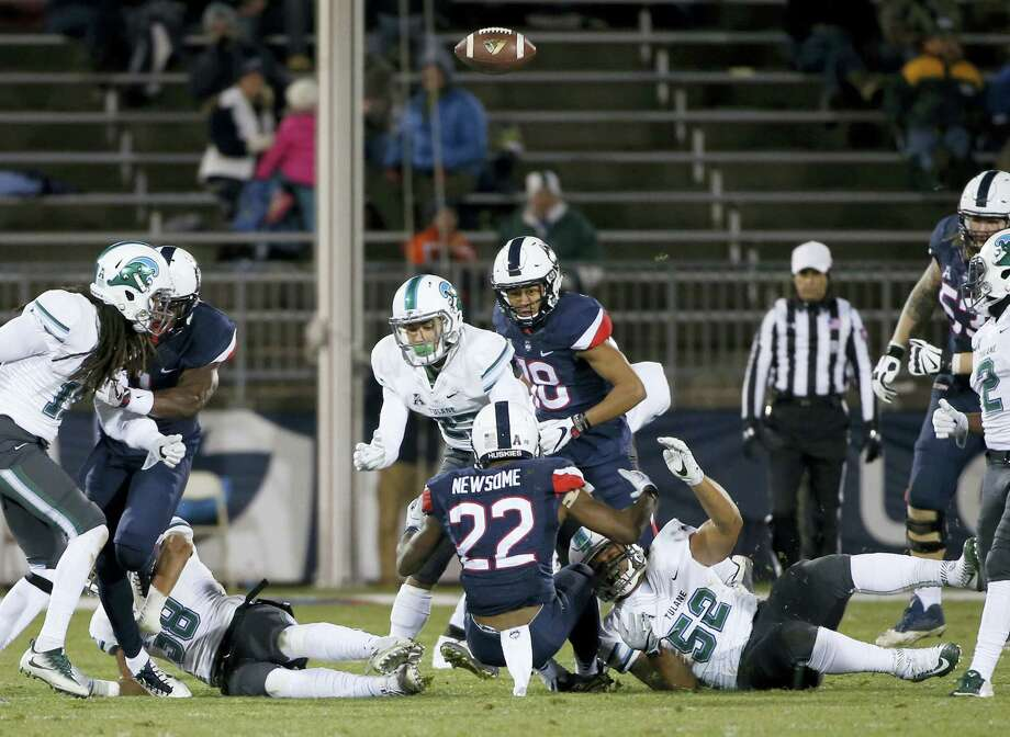 UConn running back Arkeel Newsome (22) fumbles the ball during the first half against Tulane on Saturday. Photo: Mary Schwalm — The Associated Press  / FR158029 AP