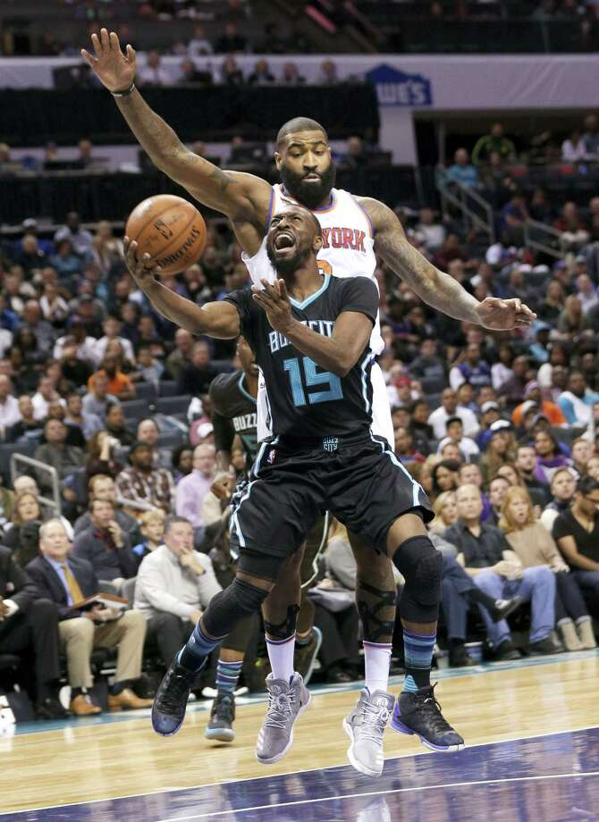 Kemba Walker (15) drives past the Knicks' Kyle O'Quinn in the first half Saturday. Photo: Chuck Burton — The Associated Press  / Copyright 2016 The Associated Press. All rights reserved.