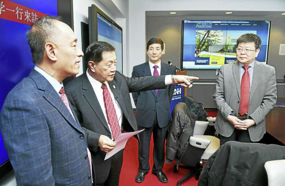 Baosheng Zhang (far left), retired Vice President of the China University of Political Science and Law, speaks with Henry Lee (left), founder of UNH's Henry C. Lee College of Criminal Justice and Forensic Sciences, before a press conference and signing ceremony for the formation of the China-U.S. Forensic Technology Research Center on 1/26/2016. Photo: ARNOLD GOLD — NEW HAVEN REGISTER