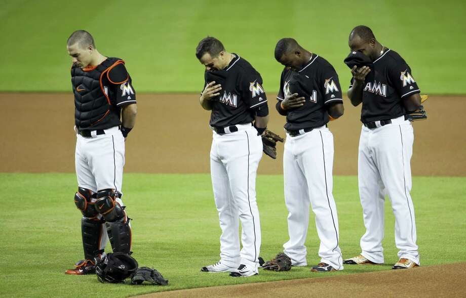 Miami Marlins catcher J.T. Realmuto, left, third baseman Martin Prado, second from left, shortstop Adeiny Hechavarria, second from right, and left fielder Marcell Ozuna, right, stand during a pre-game ceremony honoring pitcher Jose Fernandez before a baseball game against the New York Mets on Sept. 26, 2016 in Miami. Fernandez died in a boating accident Sunday. Photo: AP Photo/Lynne Sladky  / AP