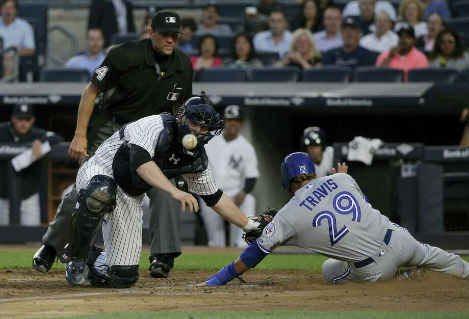 The ball, a double hit to right field by Toronto Blue Jays' Ryan Goins pops out of New York Yankees catcher Brian McCann's glove as he attempts to put the tag on Toronto Blue Jays' Devon Travis (29) during the fourth inning Wednesday in New York. Travis was safe on the play. Kevin Pillar also scored. Photo: JULIE JACOBSON — The Associated Press  / AP