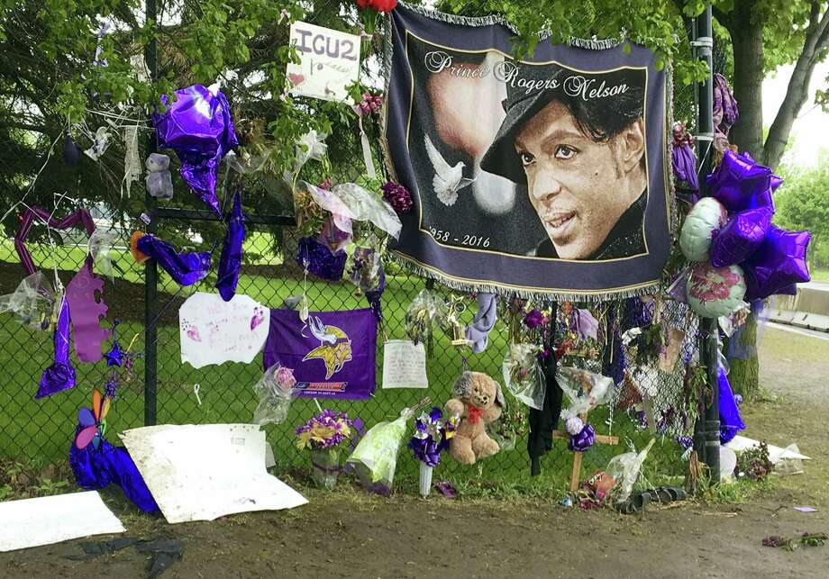 In this May 11, 2016, file photo, items left by fans at a memorial for Prince hang from a fence outside the musician's Paisley Park estate in Chanhassen, Minn. Work to settle the estate of the late rock superstar is moving forward, though a closed hearing is expected this week to resolve an undisclosed dispute between the likely heirs and the trust company that's managing the estate. Prince died of an accidental painkiller overdose in April. Photo: AP Photo/Jeff Baenen, File   / Ap