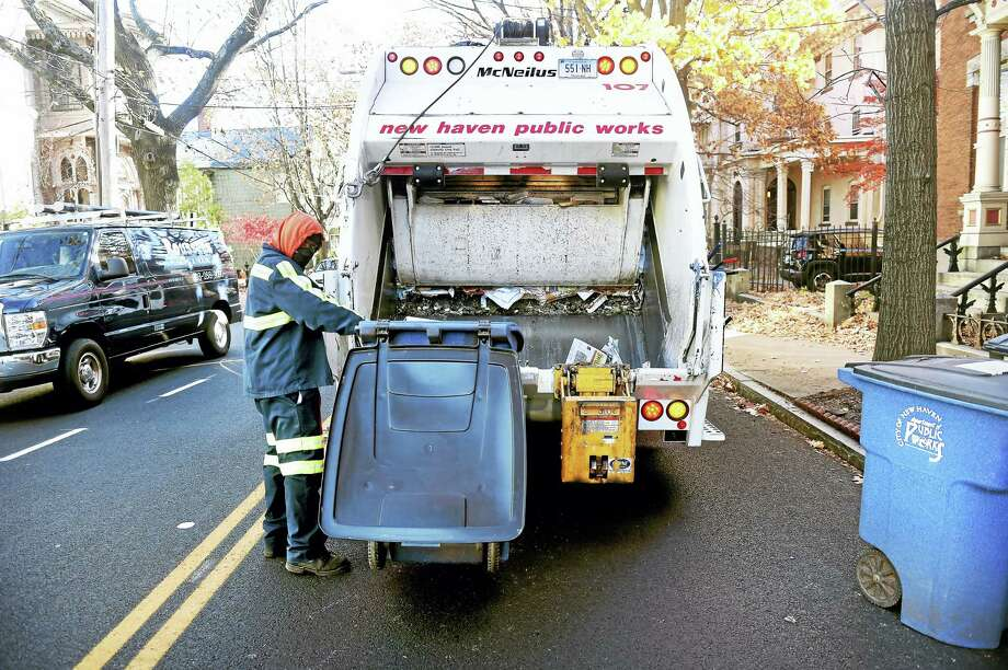Thomas Dennie of the New Haven Public Works Department collects trash on Chapel Street in New Haven. Photo: Arnold Gold — New Haven Register
