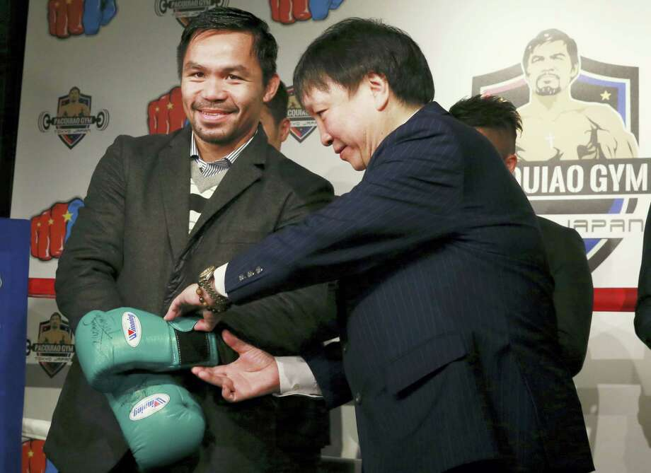 Filipino boxer Manny Pacquiao, left, gets help taking off his gloves during a press conference in Tokyo on Friday. Photo: Eugene Hoshiko — The Associated Press  / Copyright 2016 The Associated Press. All rights reserved.
