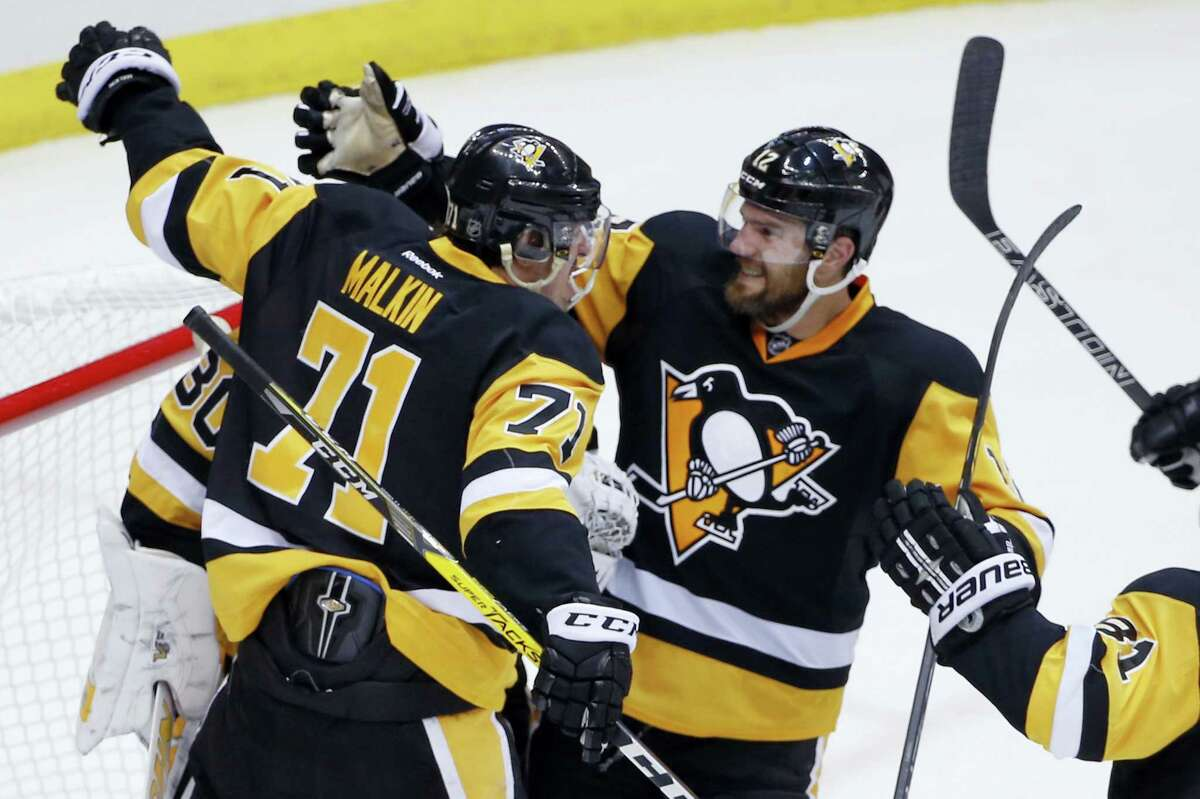 Pittsburgh Penguins' Evgeni Malkin (71) and Ben Lovejoy (12) celebrate with goalie Matt Murray (30) after Thursday's win.