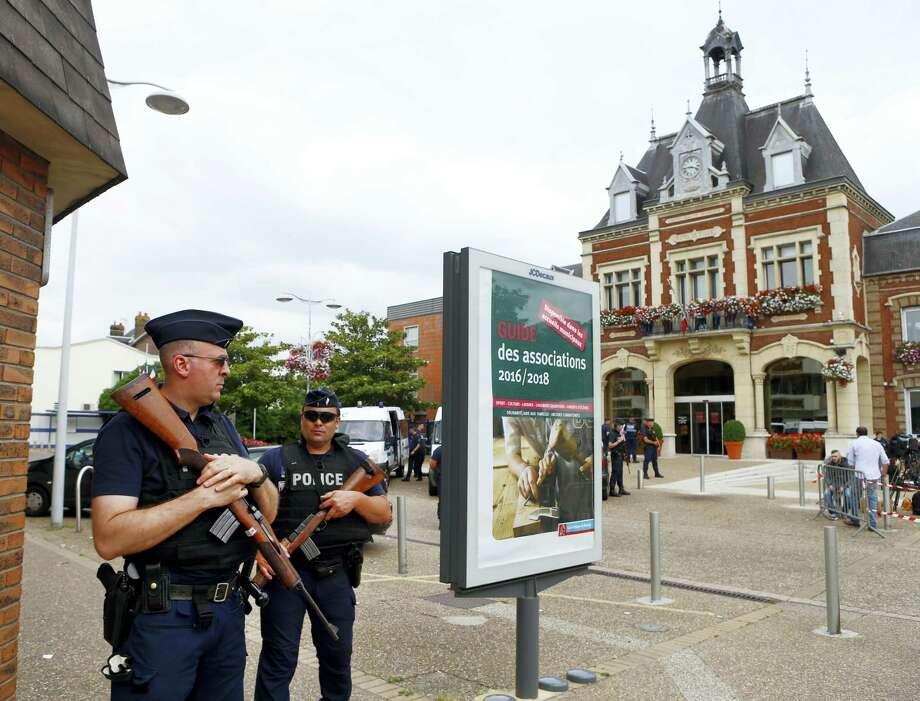 French police officers stand guard in front of the Saint-Etienne-du-Rouvray's city hall, Normandy, France, after an attack on a church that left a priest dead, Tuesday, July 26, 2016. Two attackers invaded a church Tuesday during morning Mass near the Normandy city of Rouen, killing an 84-year-old priest by slitting his throat and taking hostages before being shot and killed by police, French officials said. Photo: AP Photo/Francois Mori   / AP