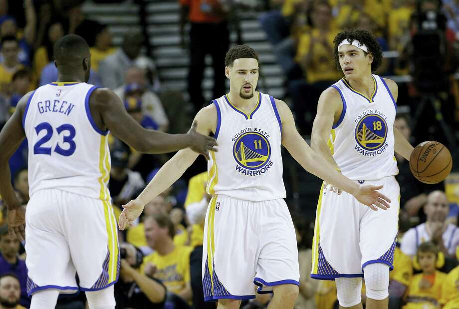 Warriors guard Klay Thompson (11), forward Draymond Green (23) and forward Anderson Varejao (18) celebrate after scoring on Thursday night. Photo: Marcio Jose Sanchez — The Associated Press  / AP