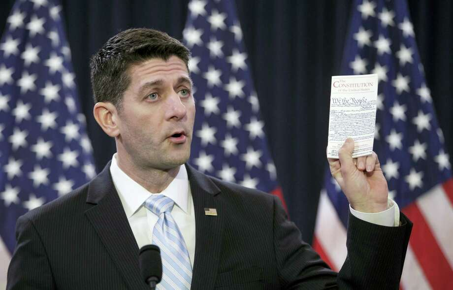 House Speaker Paul Ryan of Wis. holds a copy of the Constitution as he decries ugliness and divisiveness in American politics, delivering a veiled but passionate rebuke to GOP presidential front-runner Donald Trump and the nasty tone of the presidential campaign as he addressed congressional interns, Wednesday, March 23, 2016, on Capitol Hill in Washington. Photo: AP Photo — J. Scott Applewhite / AP