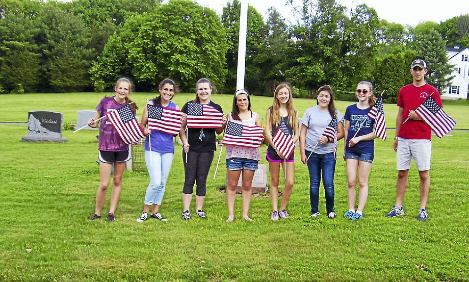 Portland High School students placed flags at the veterans graves in cemeteries throughout town earlier this week. Shown are, from left, Ashley Benham, Sarah Donahue, Morgan Benham, Katherine Donahue, Gracie Berthiaume, Alicia, Archuleta, Rebecca Tripp and Andrew Donahue, who is on leave from the USMA. Photo: Courtesy Photo
