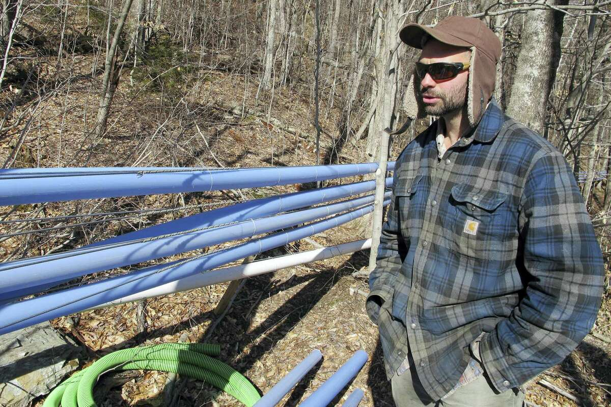 Mike Chiberton, general manager of Crown Maple's southern Vermont operation, stands near sap and vacuum lines running to maple trees in Sandgate, Vt. The company bought 4,500 acres in southern Vermont and trucks the sap to New York to be processed into maple syrup.