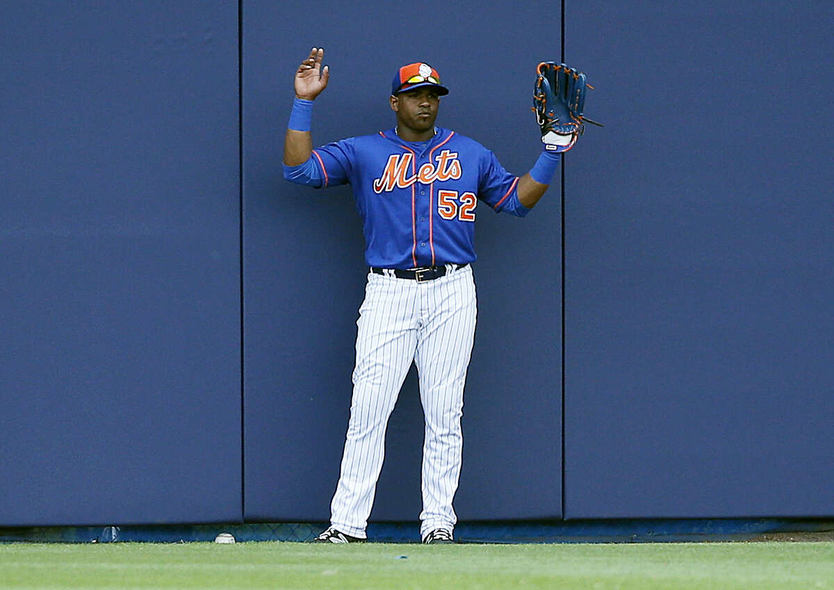 New York Mets' left fielder Yoenis Cespedes, holds up his hands pleading for a ground rule double after Houston Astros' A.J. Reed hit a ball that was stuck under the wall during the second inning of a spring training baseball game, Thursday, March 24, 2016, in Port St. Lucie, Fla. (AP Photo/Brynn Anderson)