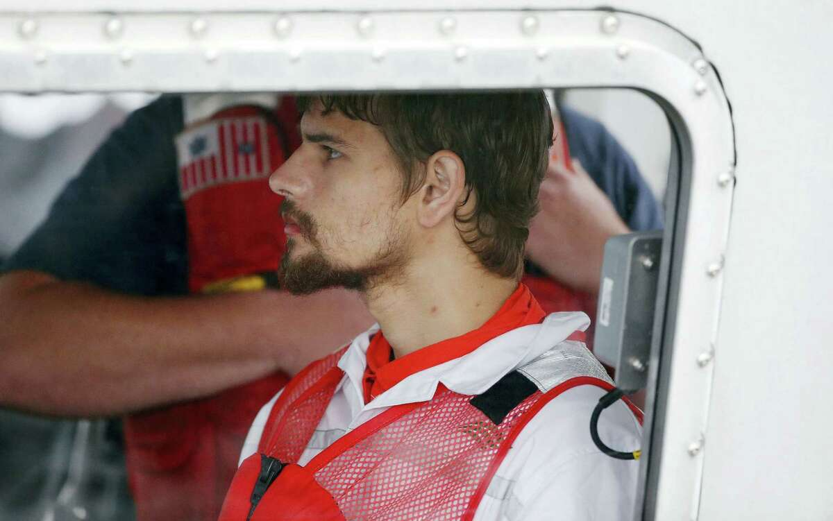 Nathan Carman arrives in a small boat at the U.S .Coast Guard station in Boston Tuesday. Carman, who formerly lived in Middletown and now has a home in Vermont, spent a week at sea in a life raft before being rescued by a passing freighter.
