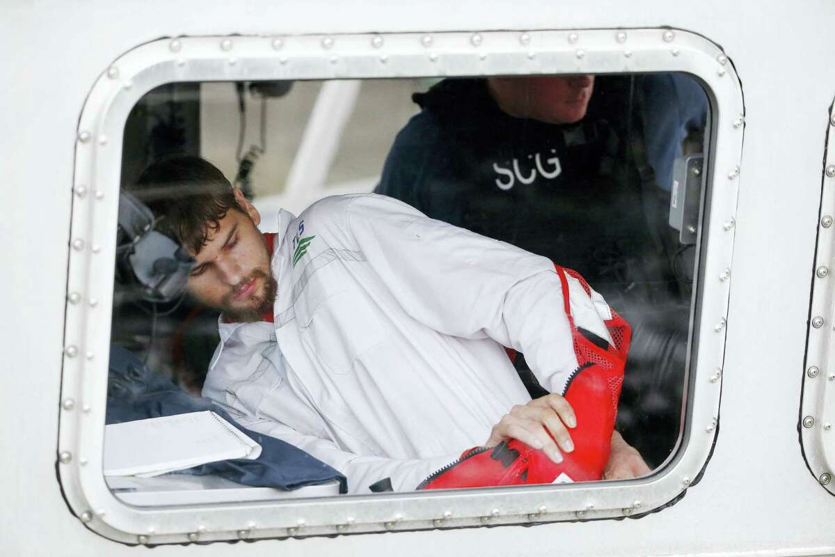 Nathan Carman prepares to disembark from a small boat at the U.S. Coast Guard station in Boston Tuesday. Carman, who formerly lived in Middletown and now has a home in Vermont, spent a week at sea in a life raft before being rescued by a passing freighter.