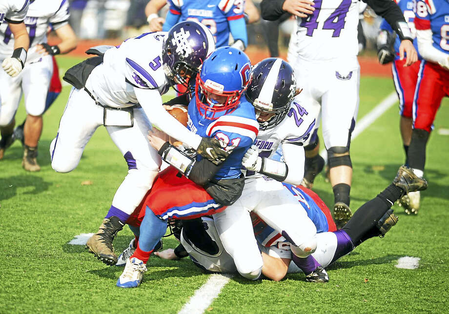 Coginchaug senior Rick Sorensen is tackled by North Branford's Charles Walcott (5) and Nick Mancini (24) on Thanksgiving Day in Durham. Photo: Jimmy Zanor - The Middletown Press