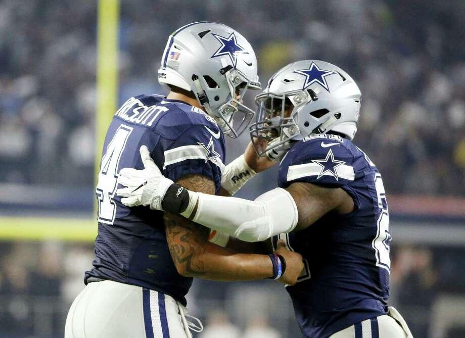 Dallas Cowboys quarterback Dak Prescott (4) and running back Ezekiel Elliott (21) celebrate a touchdown against Washington scored by Prescott on a running play in the second half. Photo: The Associated Press  / FR171331 AP