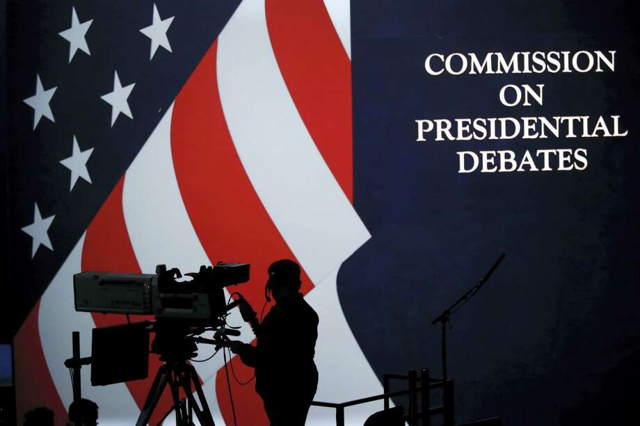 A cameraman is silhouetted against an an American flag during preparations for the presidential debate at Hofstra University in Hempstead, NY on Sept. 25, 2016. Photo: AP Photo/Mary Altaffer  / Copyright 2016 The Associated Press. All rights reserved.